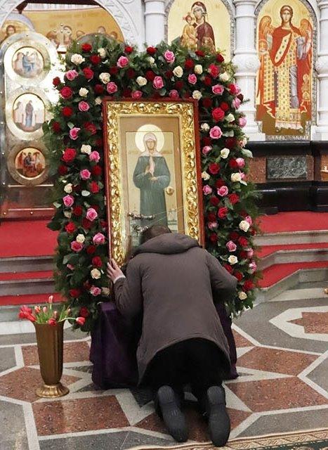 На коленях перед иконой Матроны Московской