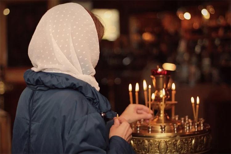Ставит свечку в храме